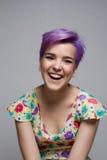 Violettes kurzhaariges Mädchen zuhause, lachend über Kamera Lizenzfreies Stockfoto