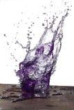 Violettes Wasserspritzen lizenzfreie stockbilder