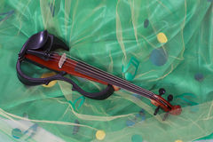 Violin. Electric violin on the green fabric decorated with notes Stock Image