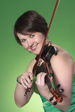 Violin. Beautiful young female violinist playing violin looking straight into camera, green background Stock Images