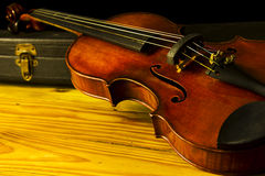 Violin. Antique violin resting on its case Stock Image