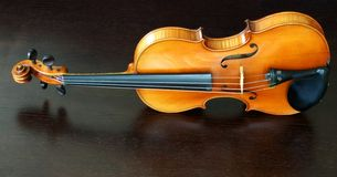 Violin. An antique violin over dark wood Stock Image