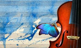 Violin on the background of the sheet music. violin on blue watercolor background closeup. beautiful blue butterfly morpho on viol