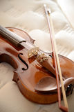 Violin On Bed. An old violin on a mattress stock photo