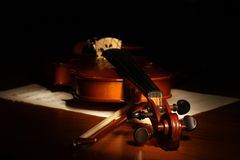 Violin on a black background. Sheet music and bow royalty free stock photo