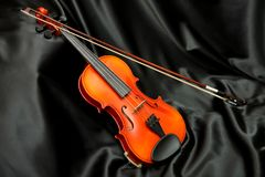 Violin and bow on black silk. Music background Royalty Free Stock Photo