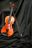 Violin and bow on black silk Royalty Free Stock Photo