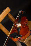 Violin. And bow on a chair, black background Royalty Free Stock Image