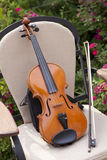 Violin and bow on a chair Royalty Free Stock Images