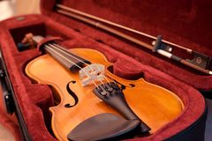 Violin and bow in dark red case. Close up view of a violin strings and bridge stock image