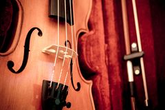 Violin and bow in dark red case. Close up view of a violin strings and bridge stock photo