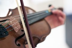 Violin and bow. Man plays violin with bow. Macro photo. Can be used as background for quotes Royalty Free Stock Image