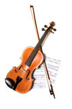Violin, bow and music. A violin and bow on top of a piece of sheet music on  white background, with copy space Stock Photography
