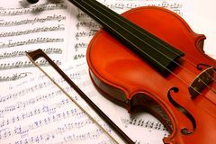 Violin with bow on music book Stock Images