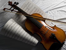 Violin with Bow music sheet. Overhead view of violin with bow on music sheet and white cloth Royalty Free Stock Images