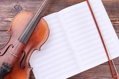 Violin, bow and musical notes. Brown violin and bow on musical sheets. Classical equipment of orchestra royalty free stock photo