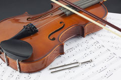Violin and bow on musical notes Royalty Free Stock Photography