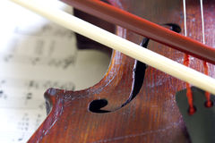 Violin bow on musical strings Stock Photo