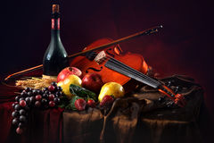 Violin with a bow on a red background next to a bottle of old wine and wet fruit Royalty Free Stock Photos