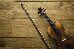 Violin and bow resting in a corner on wood floor stock photos