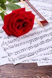 Violin bow and rose on musical notes. Music notes sheets and red rose on wooden background, vertical image. Life is the song Stock Image
