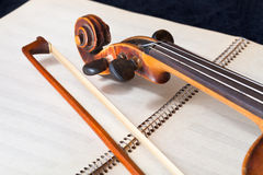 Violin bow and scroll on music book Stock Photography
