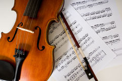 A violin and bow on sheet music. A violin and bow laying on sheet music Royalty Free Stock Photo