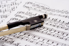 Violin bow on sheet music. Closeup of violin bow frog on pile of sheet music Royalty Free Stock Photography