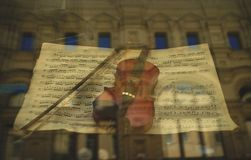 Violin and bow in a shop window, music concept royalty free stock photo