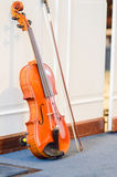 Violin and bow. A violin and a bow standing against the wall Stock Photography