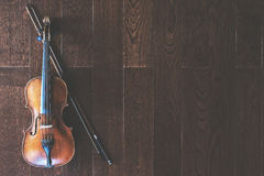 Violin with bow. Top view of violin with bow on wooden floor with copy space Stock Image