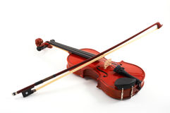 Violin with bow on white backg. Violin with bow across strings on white background, top, angled view Royalty Free Stock Photos