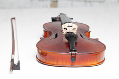 Violin with bow on the white grand piano. Horizontal Royalty Free Stock Photo