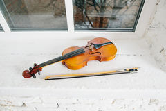 Violin and bow. On white window sill Royalty Free Stock Photography