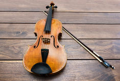 Violin and a bow on a wooden background Royalty Free Stock Images