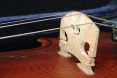 Violin Bridge. A violin bridge, held in place with the violin strings; in a blue case stock photos