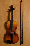 Violin and broken bow lying on the wooden floor Royalty Free Stock Photo