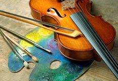 Violin, brushes and palette on a wooden background. stock image
