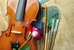 Violin, brushes, rose and palette on a wooden background. top view. Stock Image