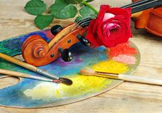 Violin, brushes, rose and palette on a wooden background. Royalty Free Stock Photos
