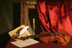 Violin, candle & feather Royalty Free Stock Images