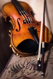 Violin, close up. A violin and its bow leans against a sofa cushion, with shallow depth of field and selective focus on the front of the violin Stock Image