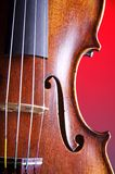 Violin Closeup Clean Red Background. A professional violin body closeup isolated against a red background in the vertical or portrait view Stock Image