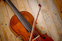 Violin closeup. Old violin and arch on a wooden background Royalty Free Stock Photo