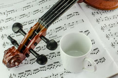 Violin and coffee cup on music sheet. Closeup od violin and coffee cup on music sheet background Stock Image