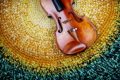 Violin on a colored knitted rug. An old violin on a colored knitted rug of warm tones stock photography