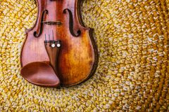 Violin on a colored knitted rug. An old violin on a colored knitted rug of warm tones stock image