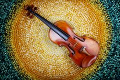 Violin on a colored knitted rug. An old violin on a colored knitted rug of warm tones stock photo
