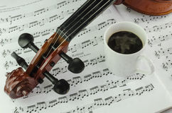 Violin and cup of coffee on music sheet. Closeup od violin and cup of coffee on music sheet background Royalty Free Stock Photography