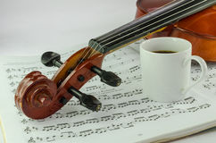 Violin and cup of coffee on music sheet. Closeup od violin and cup of coffee on music sheet background Royalty Free Stock Images
